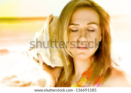 Beautiful portrait of a blond woman on the exotic beach during the sunset with a shell