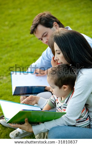Beautiful portrait of a family reading at the park