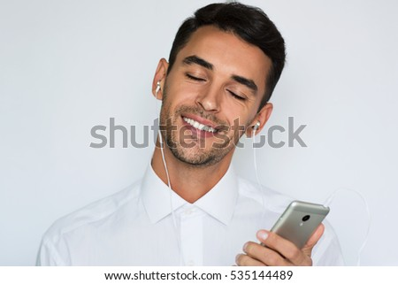 Beautiful portrait of a handsome attractive young smile man in white shirt with earphones holding mobile phone isolated on the light gray background. Happy businessman with smart phone listen music.