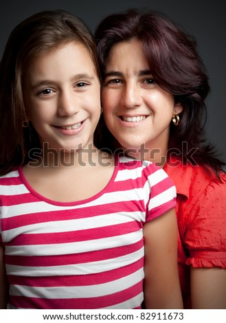 Beautiful portrait of a latin mother and her daughter on a dark background - stock photo