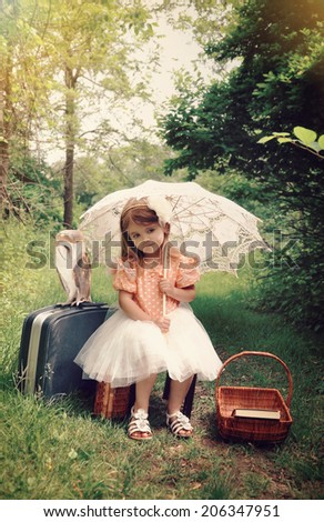 Beautiful portrait of a little girl with an umbrella and pet barn owl in the forest with a vintage look for a imagination or freedom concept. - stock photo