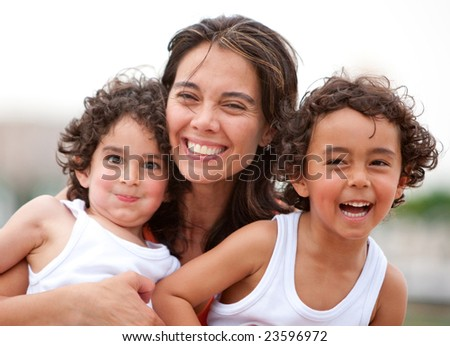 Beautiful portrait of a mother with her two sons outdoors - stock photo