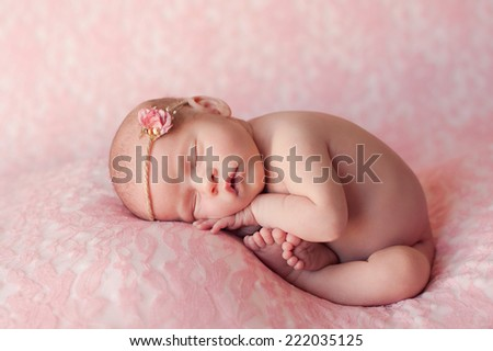 Beautiful portrait of a ten day old newborn baby girl. She is curled up and asleep on light pink lace material.