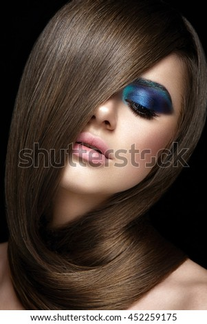 Beautiful portrait of a woman. Young model posing close up on black background with fashion hairstyle. Half face. Blue eyeshadow.