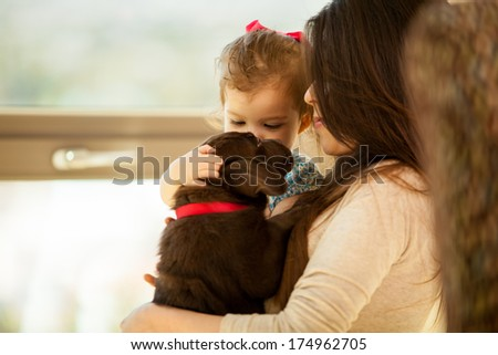 Beautiful portrait of a young woman and her daughter, both holding and petting their new Labrador puppy - stock photo