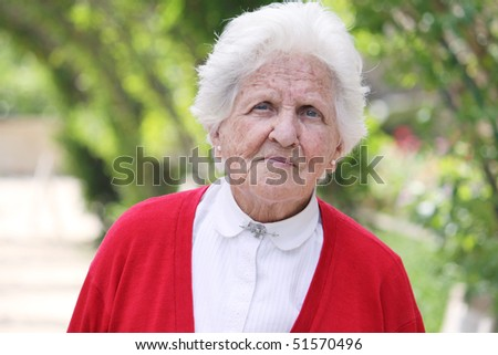 beautiful portrait of an elderly lady looking at the camera - stock photo