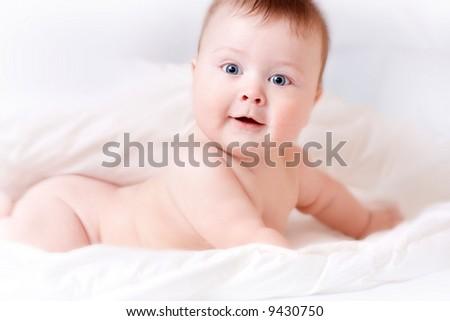 beautiful portrait of baby on white bedsheet - stock photo
