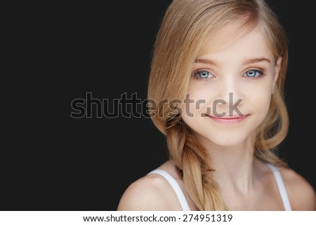 Beautiful portrait of girl with blue eyes. Isolated on dark grey background - stock photo