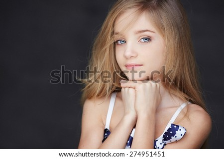 Beautiful portrait of girl with blue eyes. Isolated on dark grey background - stock photo