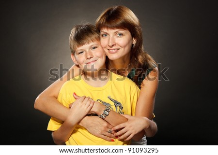 Beautiful portrait of happy cheerful mother with her son in embrace - stock photo