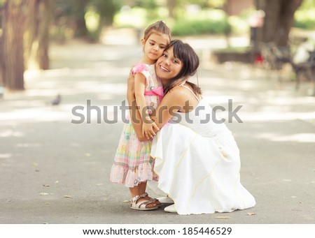 Beautiful portrait of little daughter embracing her mommy. - stock photo
