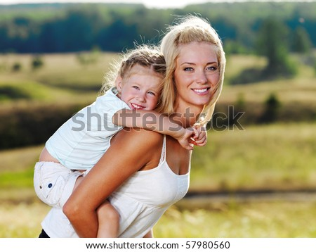 Beautiful Portrait of  mother and little pretty girl outdoors - stock photo