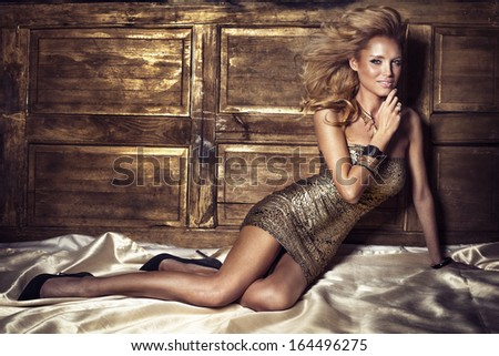 Beautiful portrait of sexy blonde woman posing in gold fashionable dress, looking at camera. - stock photo
