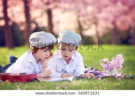 Beautiful portrait of two adorable caucasian boys, reading a book in a cherry tree blooming garden, spring afternoon, kids lying on the grass on a blanket, vase with flowers and guitar next to them - stock photo
