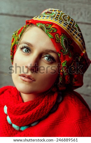 Beautiful portrait of woman in red with blue eyes and old fashion shawl and  turquoise necklace posing outdoor