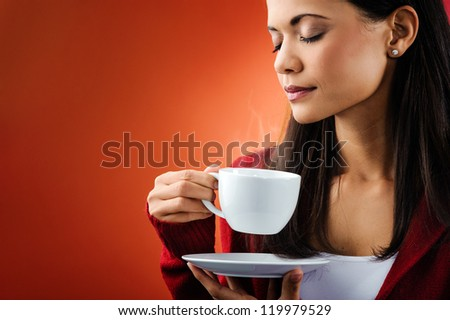 beautiful portrait of woman smelling fresh hot coffee with steam holding mug isolated on orange background - stock photo