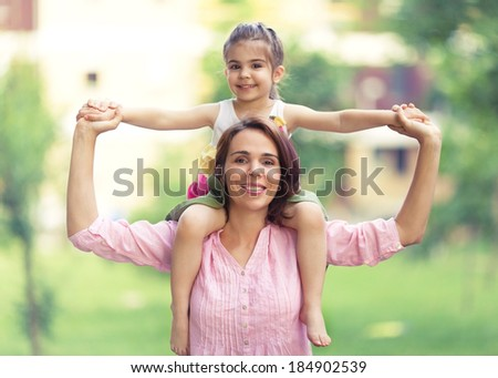 Beautiful portrait of young mother carrying little daughter on shoulders. - stock photo