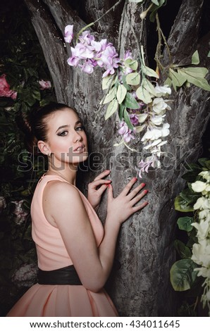 Beautiful portrait young blond girl standing near magig tree in fairy forest. Fashion female with stylish hairstyle, beauty make up, beige coctail dress. Mysterious Forest Nymph concept. - stock photo