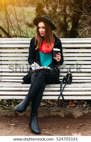 Beautiful positive girl in hat sitting on bench in sunny autumn park. Drink warm coffee and reading book outside in open air