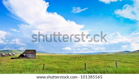 Beautiful prairie landscape with old barn and blue sky and clouds in Alberta, Canada - stock photo