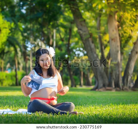 Beautiful pregnant asian woman show image of the baby