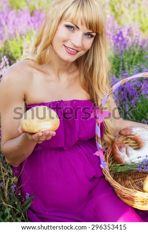 Beautiful pregnant blonde woman is wearing purple dress is holding basket with purple ribbon and sweet fresh buns and rolls