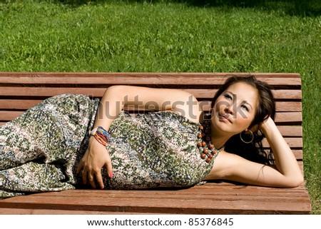 Beautiful pregnant girl lying on bench - stock photo