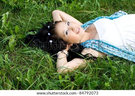 Beautiful pregnant girl lying on grass - stock photo