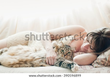 Beautiful pregnant girl sleeping on a bed with a beautiful large cat - stock photo