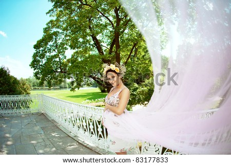 Beautiful pregnant girl with a wreath of flowers in the park - stock photo