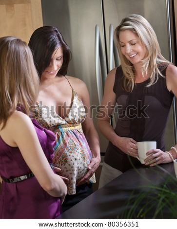 Beautiful pregnant lady with friends holds her tummy - stock photo