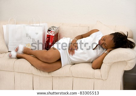 Beautiful pregnant mother laying on the couch with shopping bags - stock photo