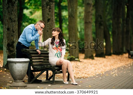 Beautiful pregnant stylish couple relaxing outside in the autumn park sitting on bench. Handsome husband kisses his wife's hand.