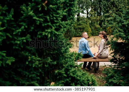 Beautiful pregnant stylish couple relaxing outside in the autumn park sitting on bench. They are lovely looking at belly. Copy space - stock photo