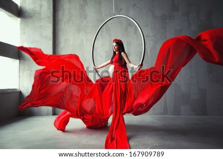 Beautiful pregnant woman acrobat in red long dress. Waving fabric. Fashion pregnancy. - stock photo
