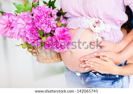 Beautiful pregnant woman. Belly of a pregnant woman. Hands of mother, father and child on a pregnant belly.