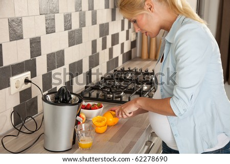 Beautiful pregnant woman cutting oranges for her breakfast
