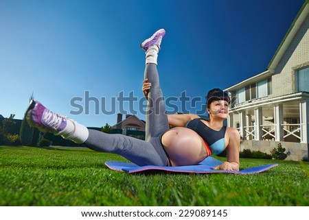 Beautiful pregnant woman doing sport near her house - stock photo