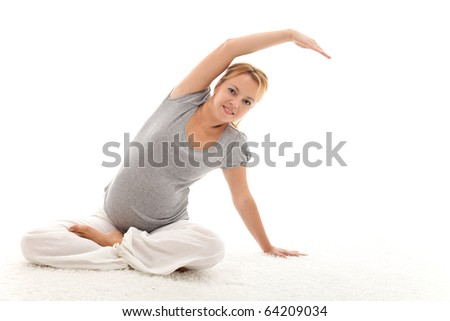 Beautiful pregnant woman doing stretching exercises sitting on the floor - isolated - stock photo