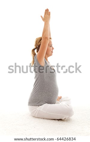 Beautiful pregnant woman doing stretching exercises while sitting - isolated - stock photo