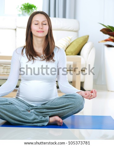 Beautiful Pregnant Woman Doing Yoga at Home. Relaxation - stock photo