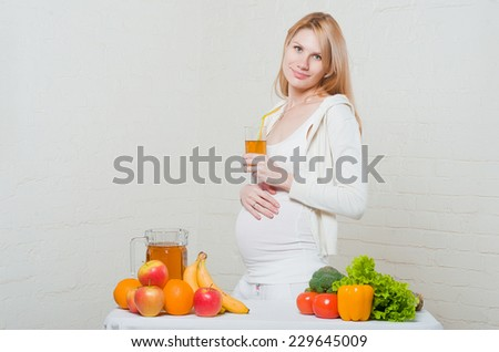 Beautiful pregnant woman drinking apple juice at home - stock photo
