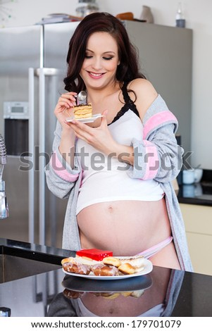 beautiful pregnant woman eating cake - stock photo