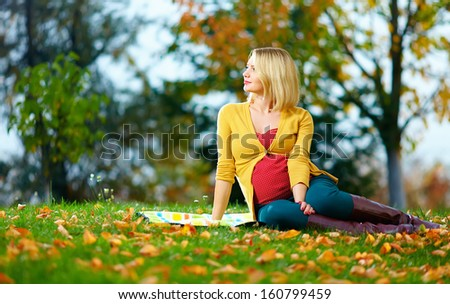 beautiful pregnant woman enjoying autumn park