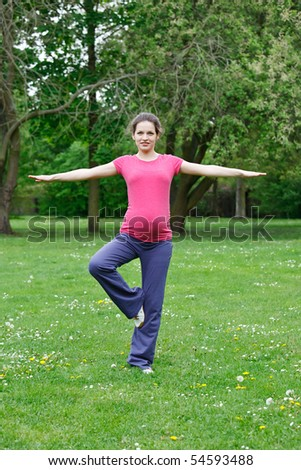 Beautiful pregnant woman exercising in the park - stock photo