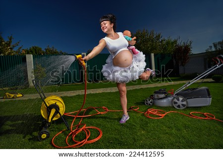 Beautiful pregnant woman having fun with garden hose splashing summer rain. - stock photo