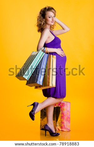 Beautiful pregnant woman holding shopping bags isolated on yellow background