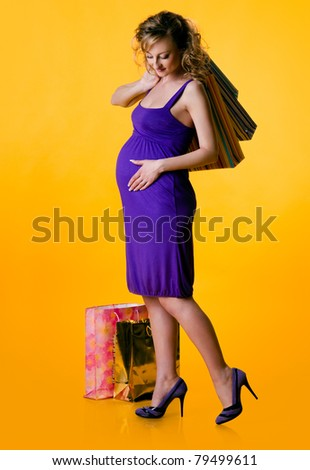 Beautiful pregnant woman holding shopping bags isolated on yellow background - stock photo