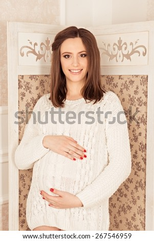 beautiful pregnant woman hugging her tummy - stock photo