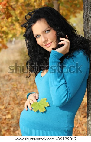 Beautiful pregnant woman in blue jacket relaxing in the autumn park - stock photo